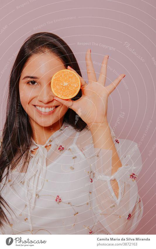 Modell, das eine Orange hält. Studioaufnahme mit rosa Hintergrund. schön Schönheit Pflege Zitrusfrüchte Nahaufnahme Kosmetik Gesicht frisch Frucht Mädchen