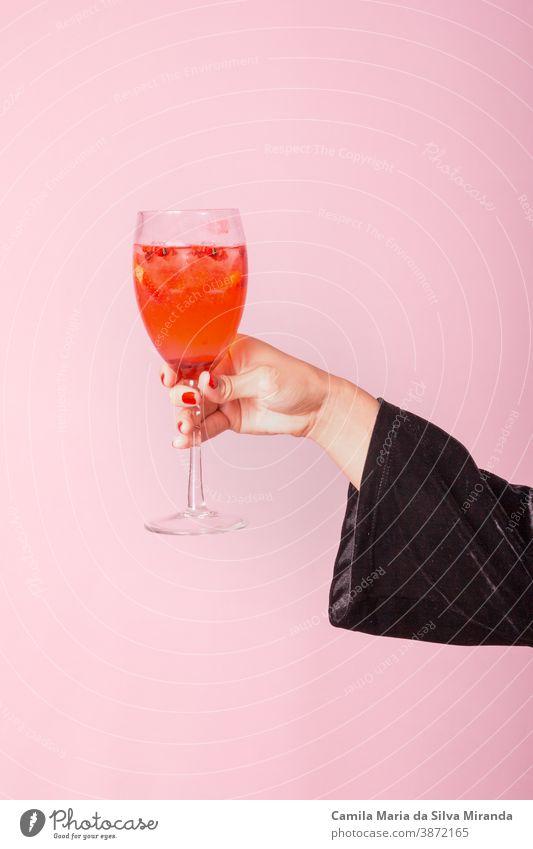 Weibliche Hand hält Tasse mit rotem Getränk. Rosa Hintergrund. Lifestyle Nahaufnahme frisch Frau trinken Zitrusfrüchte Feier Cocktail Feiertag Beteiligung