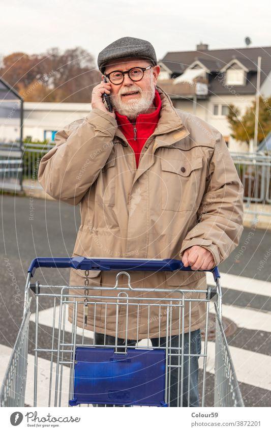 Seniorin mit Wintertuch beim Telefonieren Verbraucher bezahlen Kaufhof attraktiv Käufer im Freien Lifestyle Markt Person Smartphone benutzend Funktelefon jung