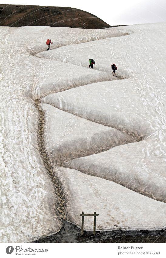 Drei Wanderer auf einem gewundenen Pfad in Island mit Spuren einer Abkürzung, die von anderen Wanderern genommen wurde Weg Serpentinenstraße Zickzack Konzept