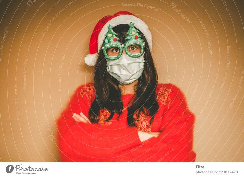 Junge Frau in weihnachtlicher Kleidung trägt Mundschutz und verschränkt die Arme vor der Brust Weihnachten Pullover rot weihnachtsmannmütze Weihnachtsdekoration