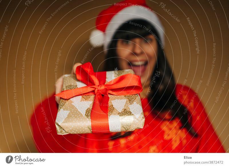 Frau mit Nikolausmütze überreicht freudig ein Weihnachtsgeschenk Weihnachten schenken Bescherung Freude euphorisch aufgeregt Weihnachten & Advent Geschenk