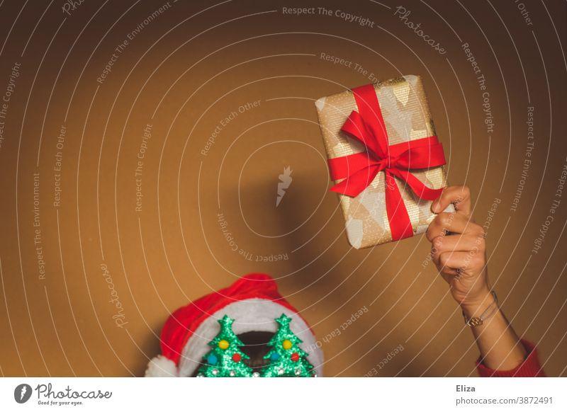 Weihnachtlich dekorierte Person hält ein Weihnachtsgeschenk Weihnachten rot weihnachtlich schenken Bescherung Weihnachten & Advent Schleife Geschenk