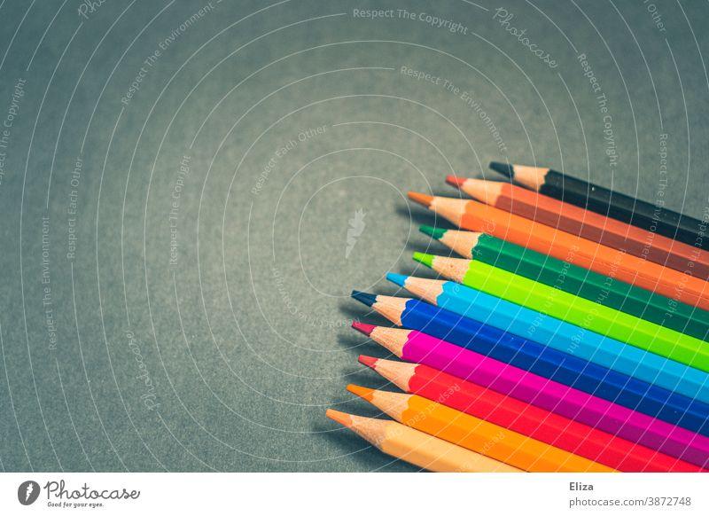 Verschiedenfarbige Buntstifte auf blaugrünem Hintergrund malen bunt verschiedene Stifte Kreativität Schreibwaren Farbstift Schule Kunst Kunstunterricht
