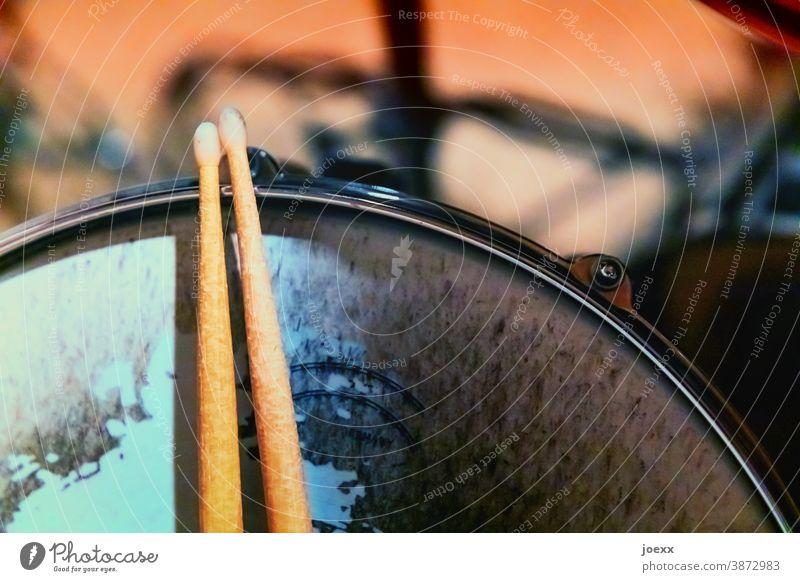 Drumsticks liegen auf Snaredrum mit stark abgenutztem Fell, schwache Tiefenschärfe Sticks Schlagzeug spielen Pause kleine Trommel Holzsticks Trommelfell