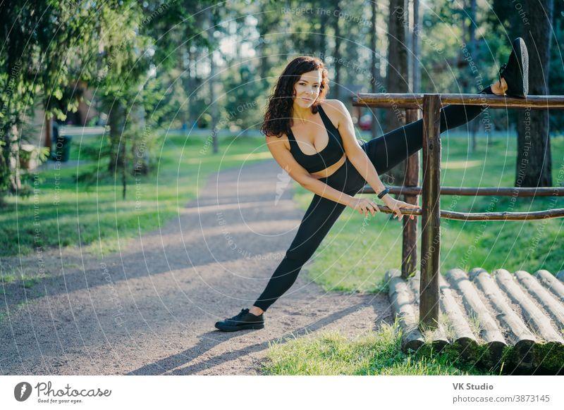 Flexible junge gelockte Frau trägt schwarze Top-Leggings und Turnschuhe, streckt die Beine, treibt an Sommertagen Sport an der frischen Luft, posiert vor grünen Bäumen. Menschen, Flexibilität und Übungskonzept
