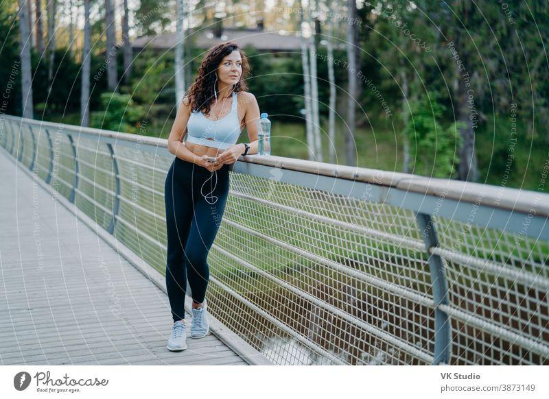 Seriöse nachdenkliche Frau mit fleckigem Körper, bekleidet mit kurz geschnittenem Top und Leggings, posiert an der Brücke, schaut nachdenklich weg, hört Musik in Kopfhörern. Menschen, gesunde Lebensweise und Fitnesskonzept