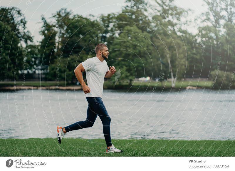 Sportler bärtiger Mann rennt durch schöne Landschaft, demonstriert Ausdauer, in aktive Kleidung gekleidet, geht am Fluss joggen, atmet frische Luft. Sport-, Bewegungs-, Fitness- und Workoutkonzept