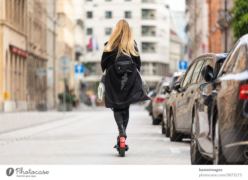 Rückansicht eines Mädchens auf einem öffentlichen Miet-Elektroroller in einer städtischen Umgebung. Neuer umweltfreundlicher, moderner öffentlicher Stadtverkehr in Ljubljana