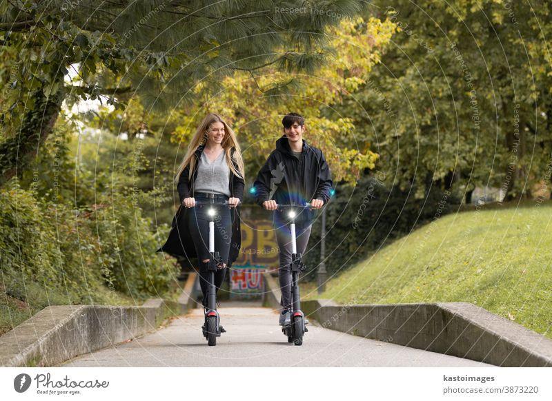 Trendige, modische Teenager, die auf öffentlichen Miet-Elektrorollern in der städtischen Umgebung fahren. Neuer umweltfreundlicher, moderner öffentlicher Stadtverkehr in Ljubljana, Slowenien