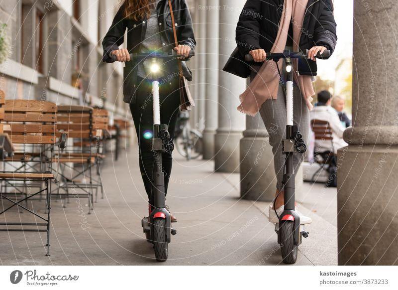 Nicht wiedererkennbare, trendige, modische, modische Teenager-Mädchen, die auf öffentlichen Miet-Elektrorollern in der städtischen Umgebung fahren. Neuer umweltfreundlicher, moderner öffentlicher Stadtverkehr in Ljubljana, Slowenien