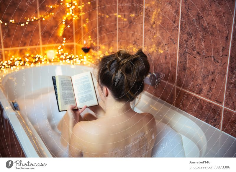 Junge schöne Frau liest ein Buch und trinkt Rotwein in der Badewanne mit Sprudelschaum, dekoriert mit bunten Lichtern, Entspannungs- und Spa-Konzept Wein jung