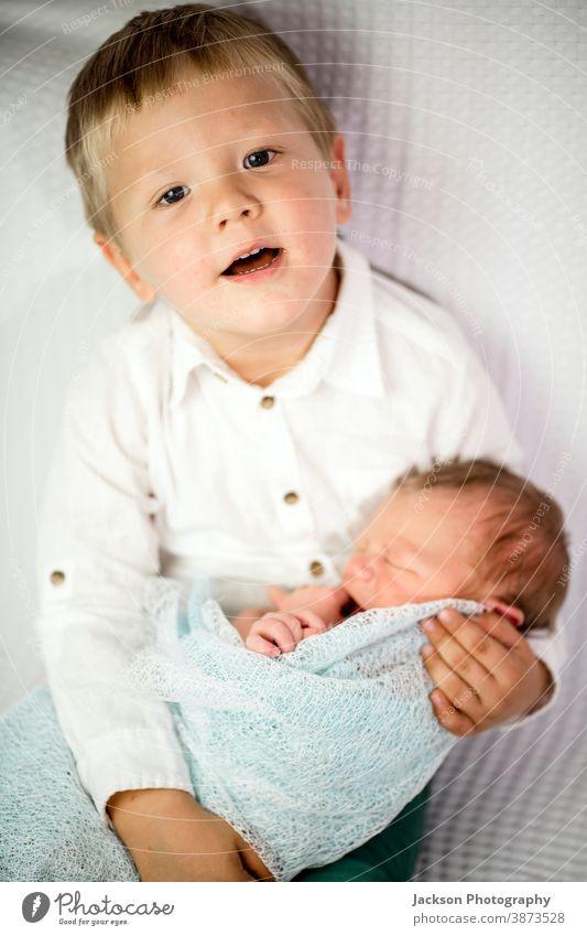 Drei Jahre alter Junge hält seinen neugeborenen Bruder Geschwister Familie Liebe Brüder Geschwisterkind umhüllen Kaukasier blond Gesicht Aussehen Lächeln