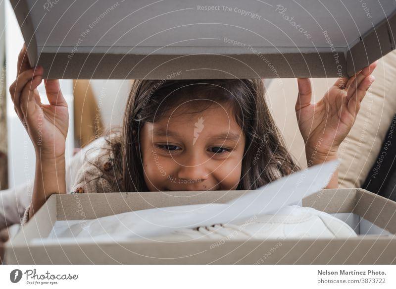Gerahmtes Foto eines niedlichen Mädchens, das eine Schachtel öffnet. träumen Menschen überrascht auspacken im Inneren Spaß Kinder spielen Hintergrund Staunen