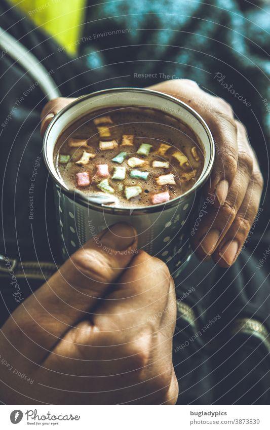 Man hält eine Tasse mit Kakao / Kaffee / Cappuccino und bunten Marshmallows in beiden Händen Kaffeetasse Kaffeetrinken Heißgetränk Getränk genießen heiß Hand