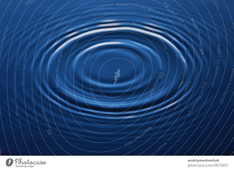 Ein Wassertropfen fällt ins Wasser und macht ein perfektes Tropfenspritzen durchsichtig Rippeln blau Reinheit winken Hintergrund abstrakt kräuselte
