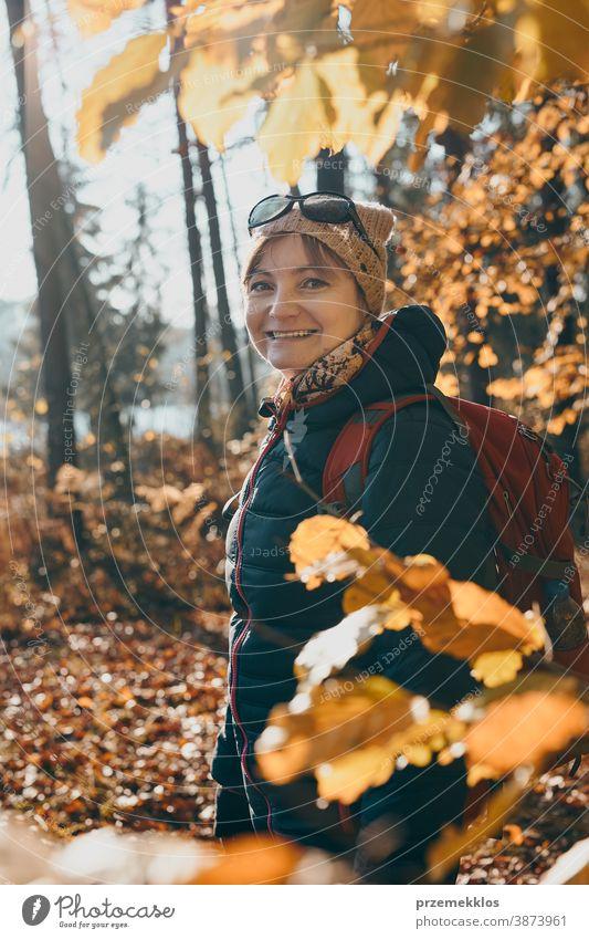 Frau mit Rucksack wandert an einem sonnigen Herbsttag in einem Wald aktiv Aktivität Abenteuer Backpacker Ausflugsziel genießen Erkundung erkunden fallen