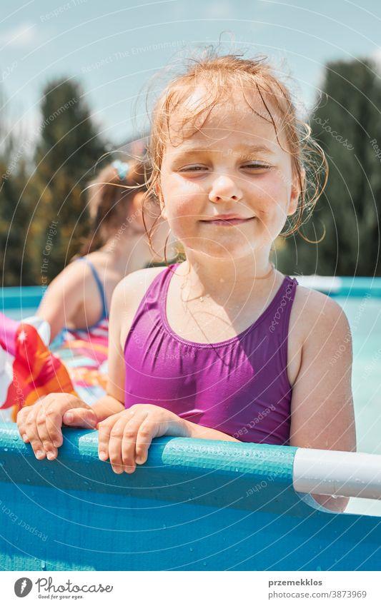 Porträt eines glücklich lächelnden Mädchens, das an einem sonnigen Sommertag in einem Schwimmbad steht und sich amüsiert authentisch Hinterhof Kindheit Kinder