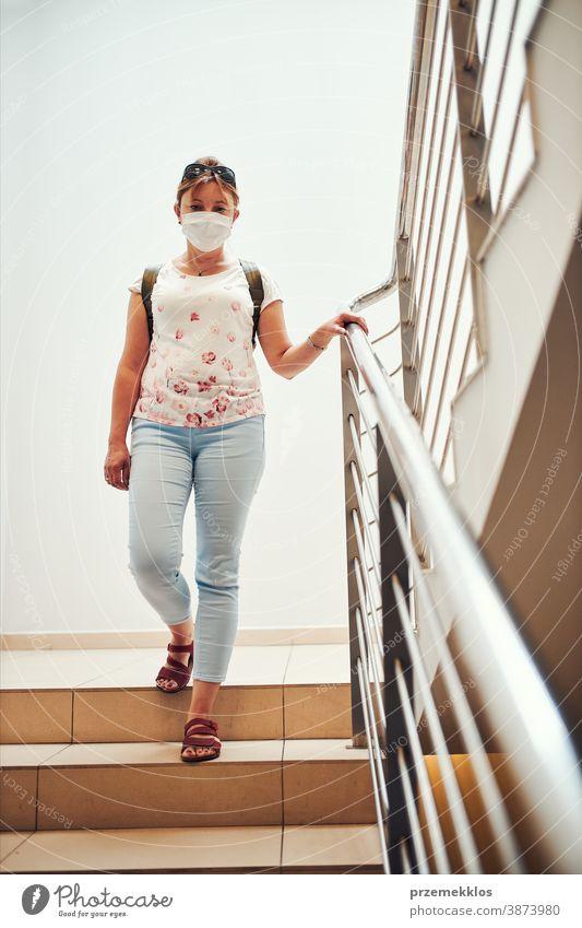 Frau geht mit Gesichtsmaske nach unten, um Mund und Nase während des Ausbruchs des pandemischen Coronavirus zu bedecken Apotheke Mundschutz covid-19 Pandemie