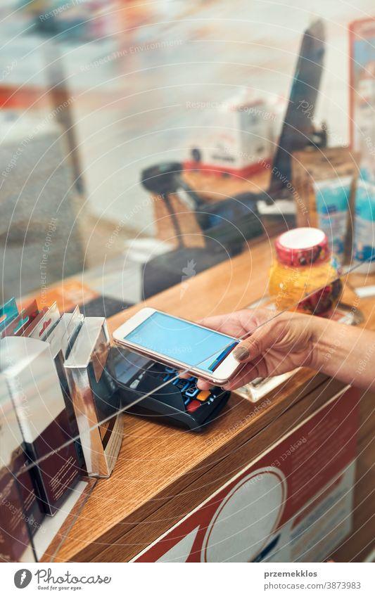 Frau bezahlt Medikamente in der Apotheke mit kontaktloser Zahlungsweise per Mobiltelefon Chemiker Werkstatt Pandemie Pflege medizinisch Drogerie im Innenbereich