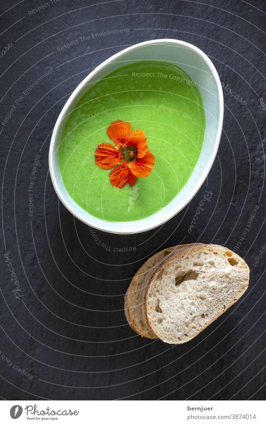cremige Erbsensuppe auf schwarzem Schiefer Suppe Hülsenfrüchte Gemüse Brei Püree oval lecker Übersicht grün gesund Essen Abendessen Sahne Kochen vegetarisch