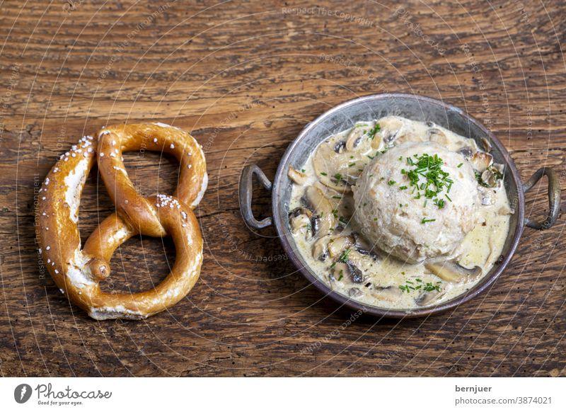 bayerischer Semmelknödel mit Sauce Breze Brezel Pilzsauce Pilzsoße Kupfer Topf Knödel Kloß Aufsicht schwammerlsoße Gericht Bayern traditionell Essen Abendessen