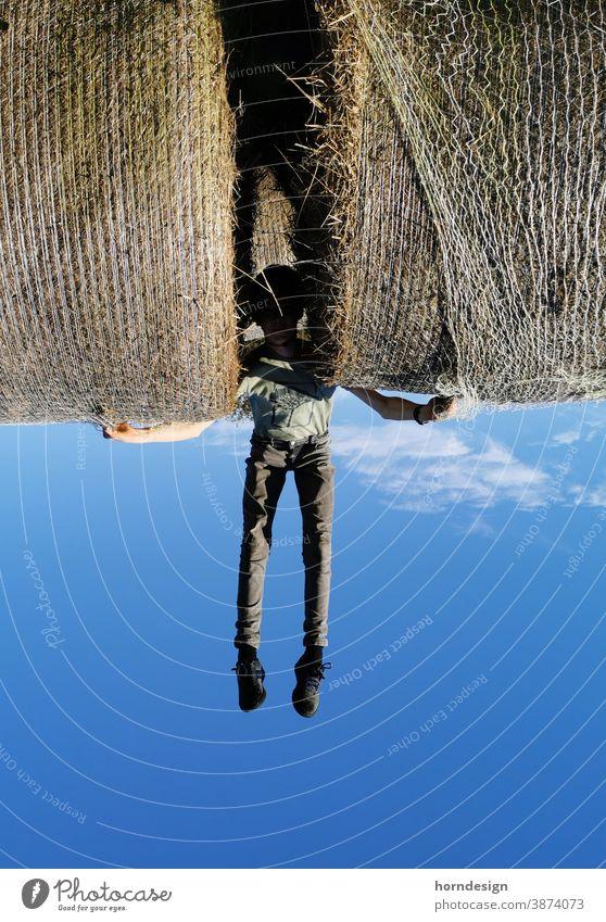 Der Heuballen Träger Fliegen Junge Superman Blau Himmel Auf dem Kopf verdreht Herkules verkehrte Welt