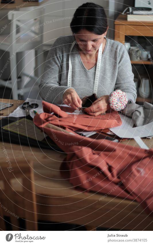 Hobbynäherin zuhause am Esstisch bei der Arbeit Nähen Handarbeit handarbeiten abstecken Schneidern Maßband Kreativität Hobbys Nadelkissen Stoff Muster Schere