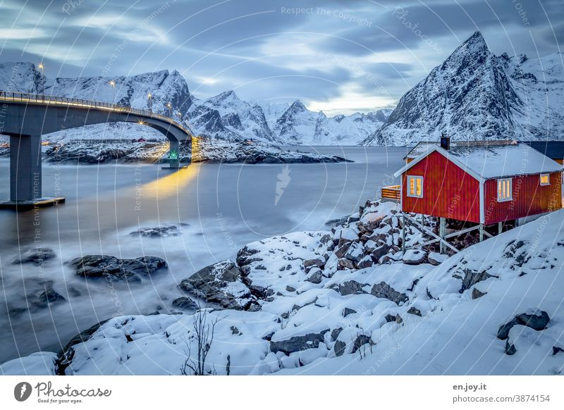 Rotes Holzhaus mit Blick auf den Reinefjord und Brücke im Winter mit viel Schnee zur blauen Stunde Lofoten Hamnøy Norwegen Skandinavien Norden Hütte Ferienhaus