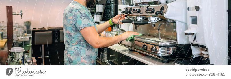 Junger Kellner beim Reinigen der Kaffeemaschine Stoff Morgen Kaffeehaus Café Transparente Netz Kopfball Panorama panoramisch unkenntlich professionell Dienst