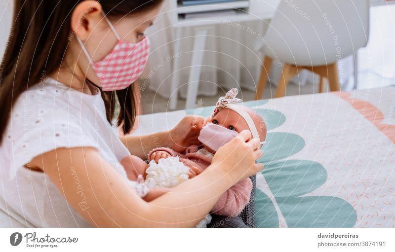 Mädchen mit Maske setzt ihrer Puppe eine kleine Maske auf Spielen Steckmaske Gesicht covid-19 Coronavirus-Erzeugung Pflege Menschen Sperrung Kind Frau