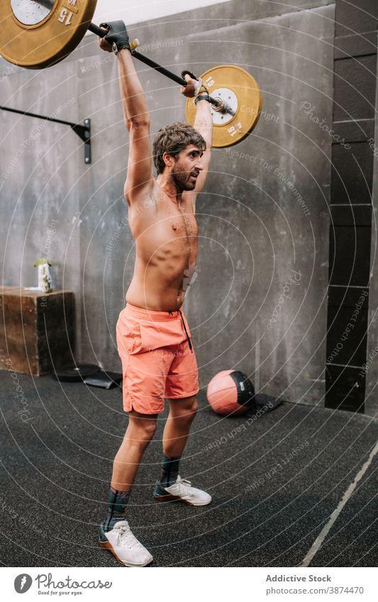 Starker Mann macht Gewichtheben Übungen mit Langhantel Stoßen und Stoßen Training Curl-Hantel Athlet muskulös Kraft männlich Gesundheit passen Stärke Körper
