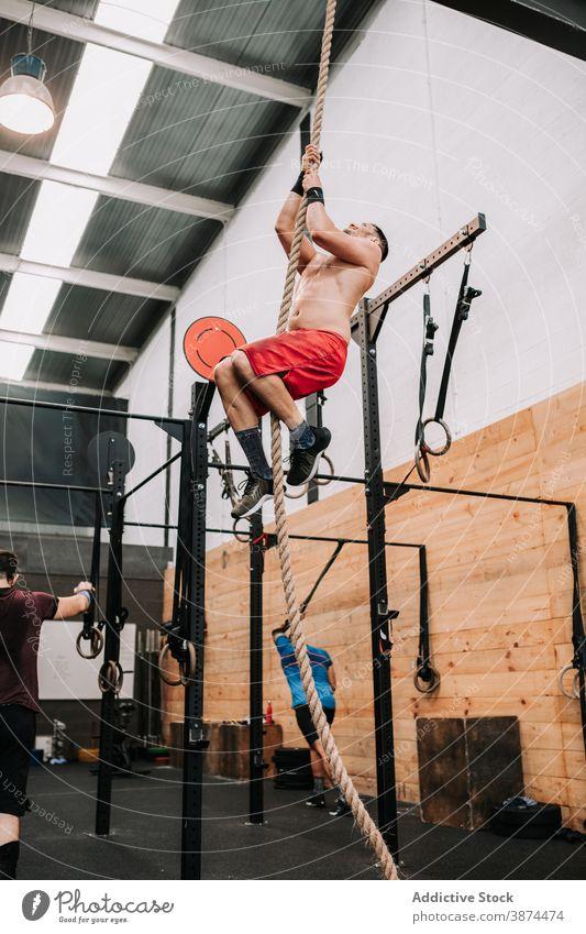 Athletischer Mann klettert Seil im Fitnessstudio Aufstieg Training operativ Sportler stark anstrengen Ausdauer männlich Motivation Aktivität Wohlbefinden