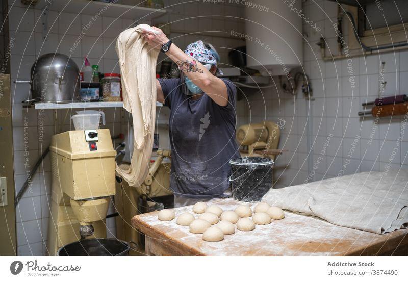Frau knetet Teig in der Backstube Brot Bäckerei roh Arbeit kneten Teigwaren vorbereiten Küche Mundschutz neue Normale Koch Lebensmittel Küchenchef frisch