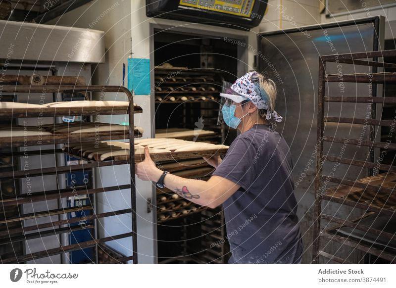 Frau bereitet Brot in der Bäckerei vor backen Ofen Koch Baguette Backblech Teigwaren roh Mundschutz Schutzschild neue Normale Coronavirus heiß Job Beruf Rezept