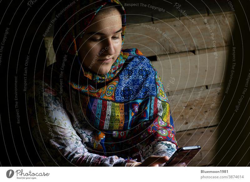 Porträt eines attraktiven muslimischen Mädchens im Teenageralter, das mit einem Smartphone arbeitet weiß Denken hell lässig Menschen Kaukasier niedlich Kleid