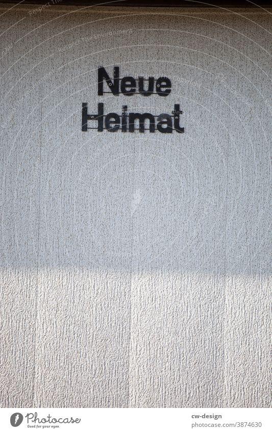 """Fassade mit Aufschrift """"Neue Heimat"""" Haus Außenaufnahme Farbfoto Mauer Gebäude Menschenleer Wand Architektur Tag Bauwerk Einfamilienhaus trist Licht Schatten"""