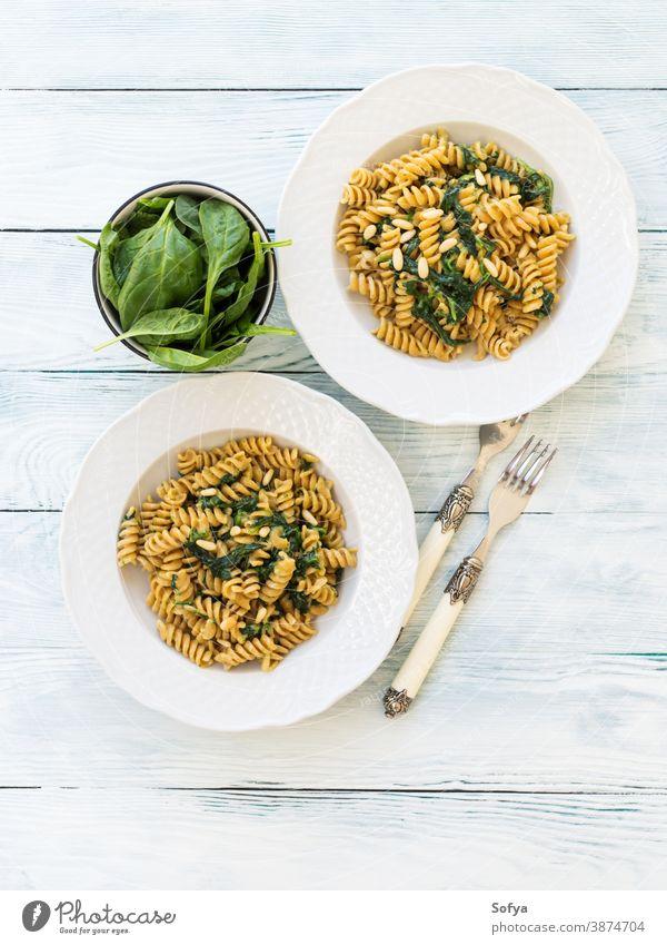 Vollkornnudeln mit Spinat und Pinienkernen Spätzle Lebensmittel Teller Tisch Holz Speise Veganer Vegetarier Blätter Italienisch Baby Mahlzeit rustikal organisch