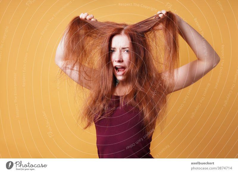 zum Haare raufen - frustrierte junge Frau Verzweiflung Haarpflege Wutausbruch bad hair day Tag der schlechten Haare Frustration schreien Emotion zerzaust lustig