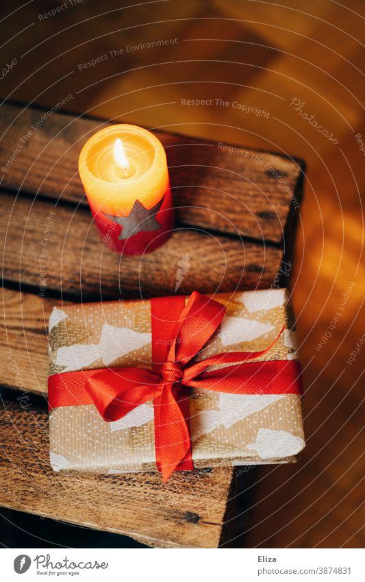 Weihnachtsgeschenk neben brennender Kerze Weihnachten Weihnachtsstimmung schenken Geschenk Kerzenschein brennende Kerze Weihnachten & Advent Überraschung rot