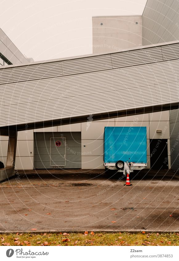Industriehalle mit geparktem Anhänger anhänger fahrzeuganhänger industrie industriehalle tor architektur produktion parkplatz parken grau weiß clean linien