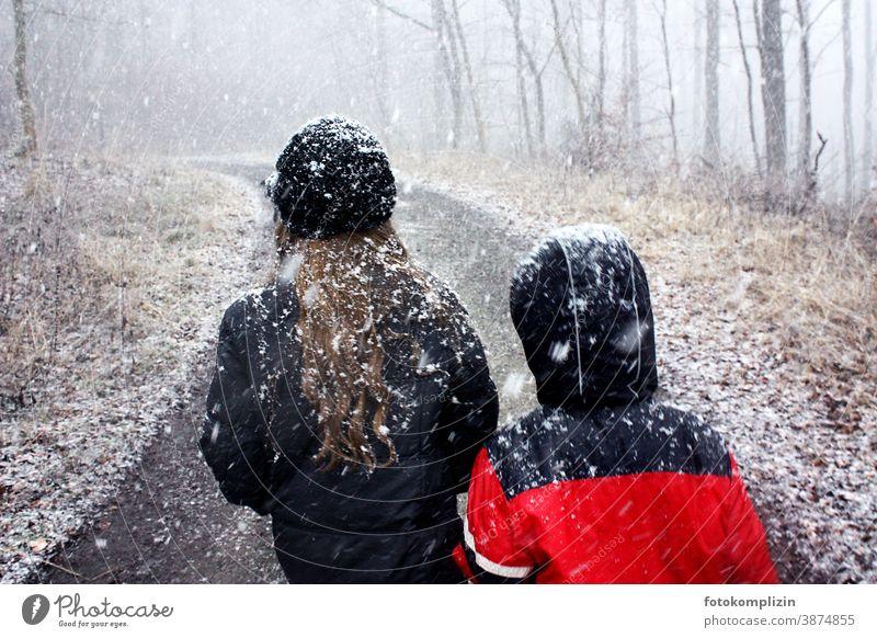 zwei Kinder auf einem Waldweg während es schneit Schneefall Schneeflocke Winter ein Kind sein Wintereinbruch zugeschneit Kindheit Schneeflocken Schneelandschaft