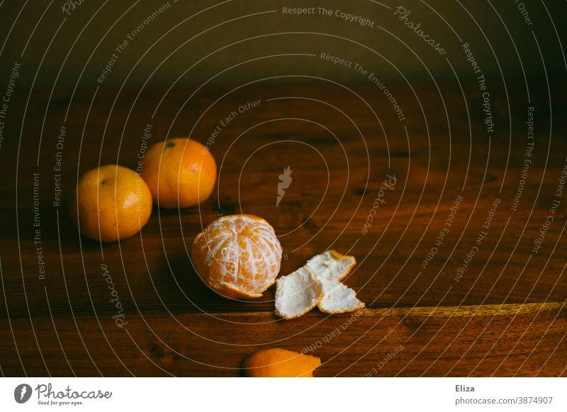 Drei Mandarinen, davon eine geschält, auf einem Holztisch Tisch gesund Winter Advent Obst Vitamin C Gesundheit Lebensmittel Vitaminreich orange Clementine