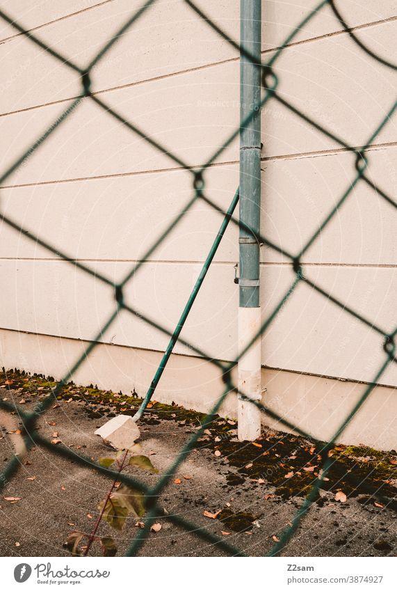 Industriefassade mit Rohren durch einen Zaun fotografiert industrie architektur industriehalle industriegebiet fabrik fabrikhalle linien minimalismus beton