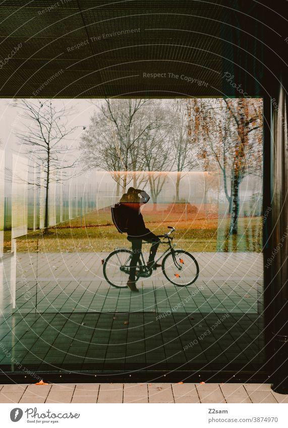 Selbstportrait eines Fotografen auf dem Fahrrad fahrrad fahrradfahren fotograf fotografieren spiegel scheibe fenster natur spiegelung herbst bäume warme farben