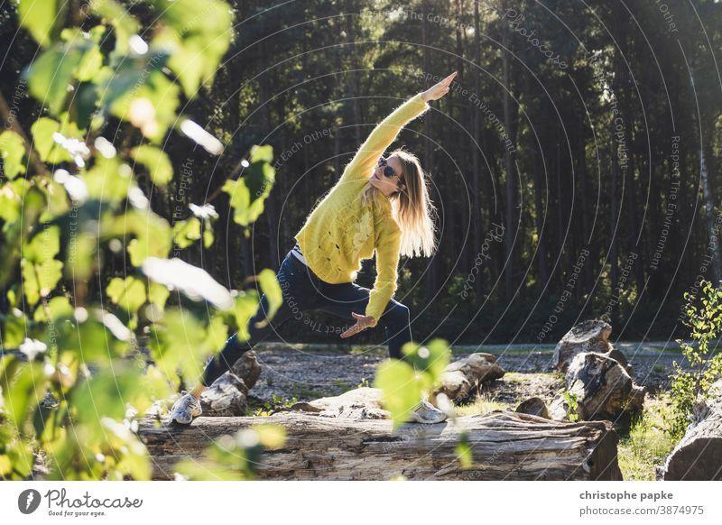 Frau macht Yoga auf Baumstamm im Wald grün Umwelt Natur Außenaufnahme Farbfoto Tag Sport Bewegung Blätter Landschaft Schönes Wetter Sonnenlicht