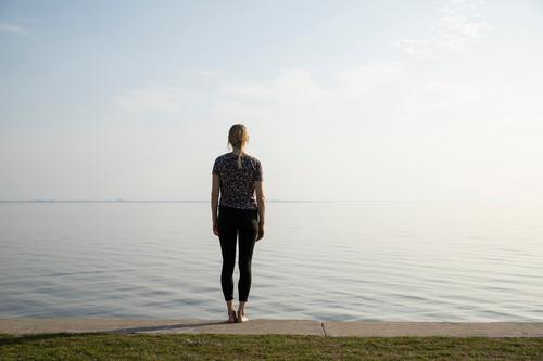 Junge Frau steht vor Meer Bodden Ferien & Urlaub & Reisen Erholung nachdenklich Ruhe Wasser Horizont ausblick Küste Natur Himmel Ferne Ostsee Menschenleer