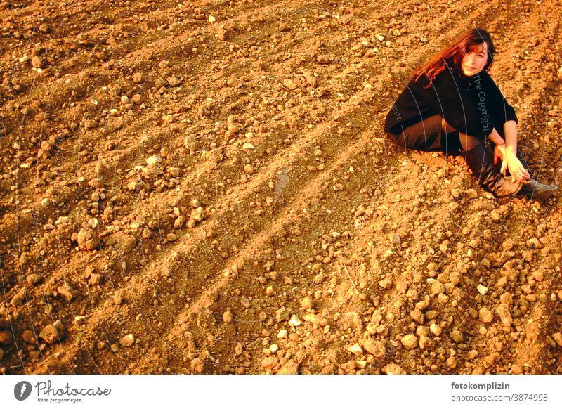 Junge Frau sitzt auf Ackerboden acker erde Dschungel Klick schauen Draussen Porträt feminin Persönlichkeit Natur Blick in die Kamera direkter Blick