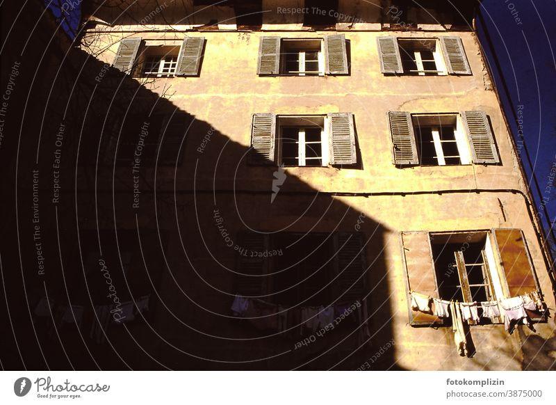 französische Altbaufassade mit Wäscheleine vor dem Fenster Fassade bauwesen architektur alt Haus Gebäude babywäsche Schatten hausschatten Frankreich südländisch