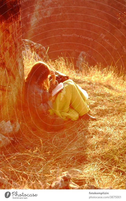 junge Frau, im Sonnenlicht an einen Stamm gelehnt, liest versunken in einem Buch Lesepause lesen Natur feminin Kälte Pause wiederherstellen einsam Ruhe